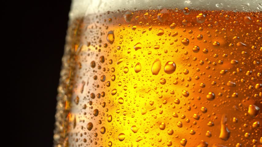 Glass of beer turns slowly around its axis. Close up 4K video. Black background. | Shutterstock HD Video #1008285271