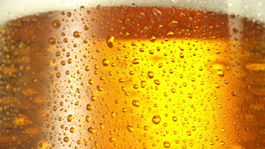 Stream of beer pours into a rotating beer glass. Close up 4K video. | Shutterstock HD Video #1008285481