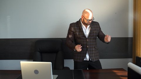 Businessman dancing excitedly at his desk in office. Young attractive Handsome business man funny dancing in office workplace. Happy young crazy businessman doing victory dance, successful achievement