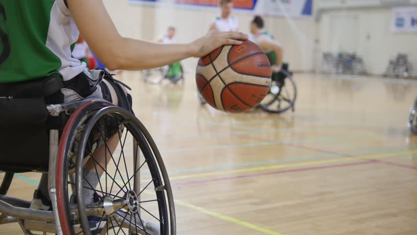 Wheelchair basketball player dribbling the ball quickly during training of disabled sportsmen | Shutterstock HD Video #1008318841