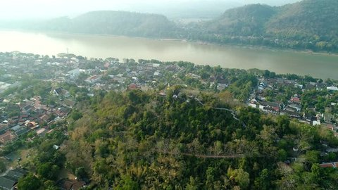 4k Video shot aerial view by drone. Historic Luang Prabang on the Mekong River in Laos. Road in the city. Home village streets.