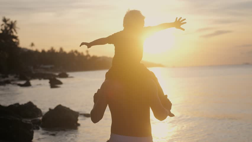Happy father and son in eyeglasses playing on tropical beach boy rising up hands imitating a flight at wonderful sunset through the shining sun. sow motion. 3840x2160