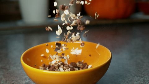 SUPER SLOW MOTION: Nutritious mixture of rolled oats, bran cereal and chocolate pieces land in orange breakfast bowl. Healthy chocolate cereal is being poured into bowl. Nourishing healthy breakfast.