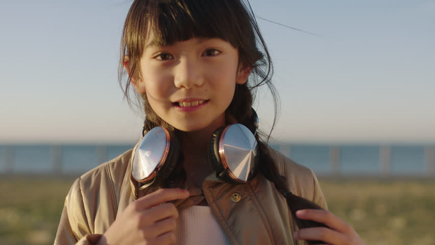 close up portrait of cheerful asian girl smiling happy playful enjoying day on seaside beach park wearing headphones cute innocent