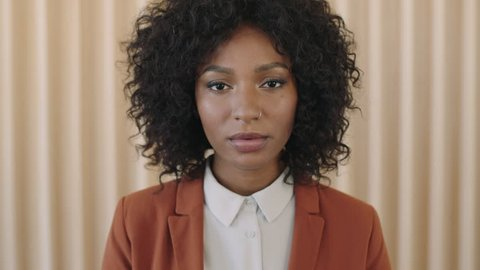 close up portrait of stylish young african american woman afro hairstyle looking serious at camera trendy black female wearing suit positive real people series