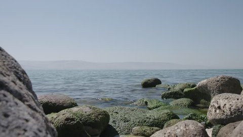 Sea of Galilee from the shore, rocks in the footage with moving water, June 7, 2017.