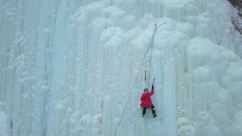 Alpinist climbs to top of huge icy wall.