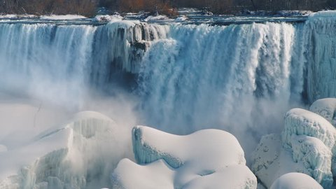 The flow of water from the Niagara River falls on the stones covered with snow and ice. Incredible winter scene at Niagara Falls. 4K slow motion video