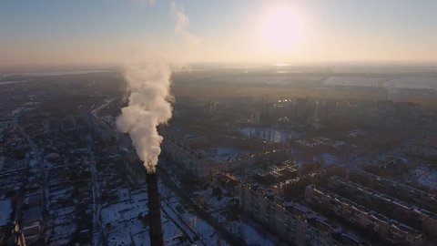 A bird`s eye view of a giant flue chimney with dense white smoke in multistoried houses in Ukraine at sunset. Drone flies away