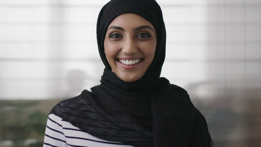 Portrait of professional young muslim business woman looking at camera laughing cheerful wearing traditional headscarf in office background close up | Shutterstock HD Video #1008367771