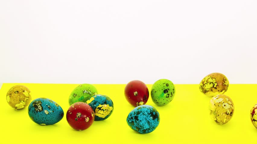 Beautiful multicolored easter eggs lie on a bright yellow background in scatter. Small and large painted Easter eggs. The egg is standing on a stand. Festive composition for Easter.