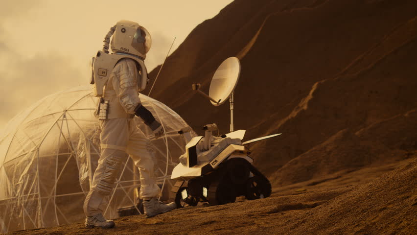 Astronaut Goes Up the Mountain to Explore Red Planet/ Mars. In the Background His Base and AI Powered Rover. Futuristic Colonization Concept. Shot on RED EPIC-W 8K Helium Cinema Camera.