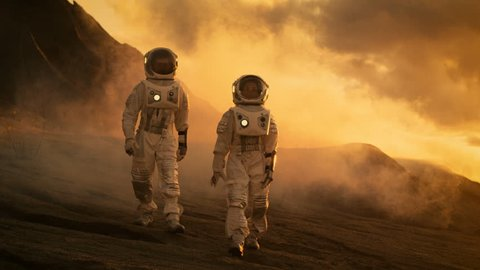 Two Astronauts in Space Suits Confidently Walking on Mars, Exploration Expedition on the Planet's Surface. Space Travel, Planet Discovery, Colonization Concept. Shot on RED EPIC-W 8K Helium Camera.