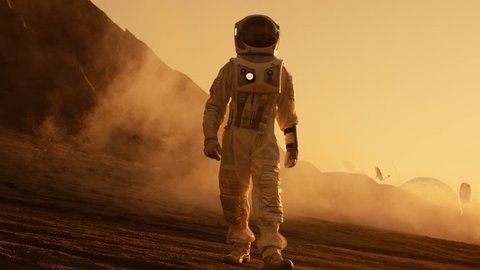 Proud Astronaut Confidently Walks on Mars Surface. Red Planet Covered in Gas and rock, Overcoming Difficulties, Important Moment for the Human Race. Shot on RED EPIC-W 8K Helium Cinema Camera.