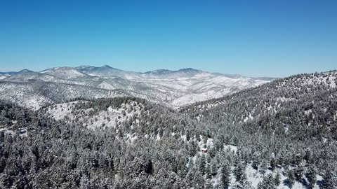 Aerial view of snow covered mountains and trees in Colorado