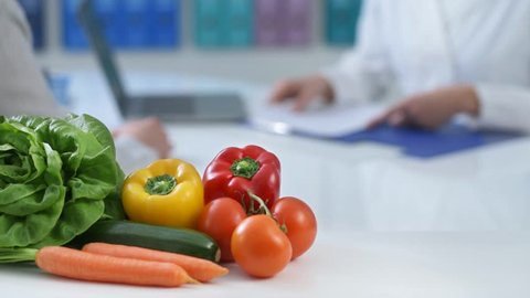 Patient meeting a professional dietician in the office and receiving a prescription diet, healthy fresh vegetables on the foreground