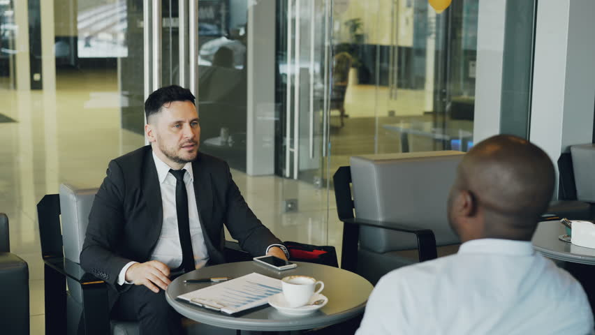 Cheerful Caucasian businessman in formal clothes smiling and discussing business profit with his African American colleague in cafe. Young waitress bringing cup of coffee. | Shutterstock HD Video #1008430891