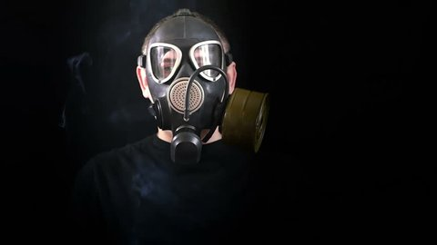 The face of a man in a gas mask on a black background that protects from smoke. Close-up