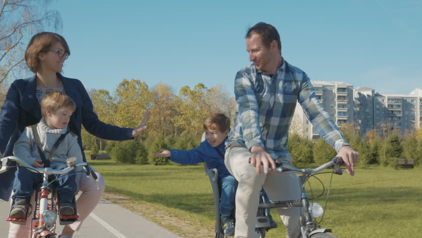Tracking shot - Family having fun riding bikes in beautiful green city park.   Shutterstock HD Video #1008441961