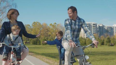 Tracking shot - Family having fun riding bikes in beautiful green city park.