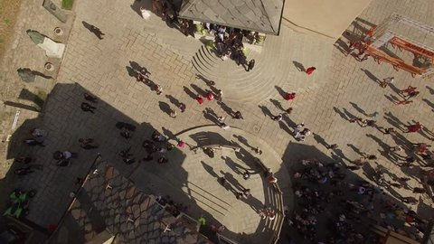 4k Crowd of people move at old European piazza center from above. Sun day group of guests stand at church stairs greeting meeting waiting low aerial drone shot. Life of small medieval town in Italy