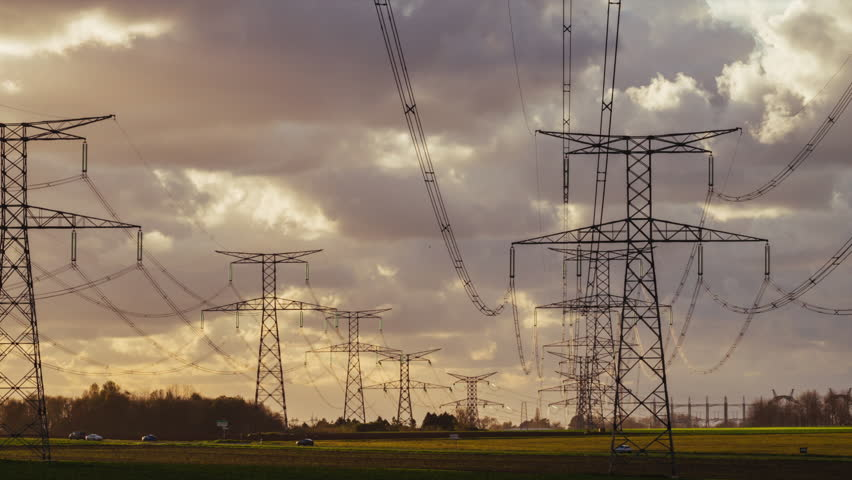 Panoramic Time lapse of high voltage power lines and transmission towers in countryside with cloudy dramatic sky in Normandy, France. Electric power industry and nature concept