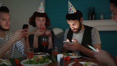 Birthday party at full speed: group of young friends sitting at table of cozy living room and wrapped up in virtual reality with help of smartphones