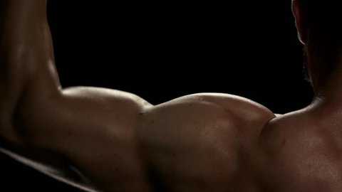 Lifting dumbbells for bigger biceps close up. Close up handsome man with big biceps lifting weigths over dark background.