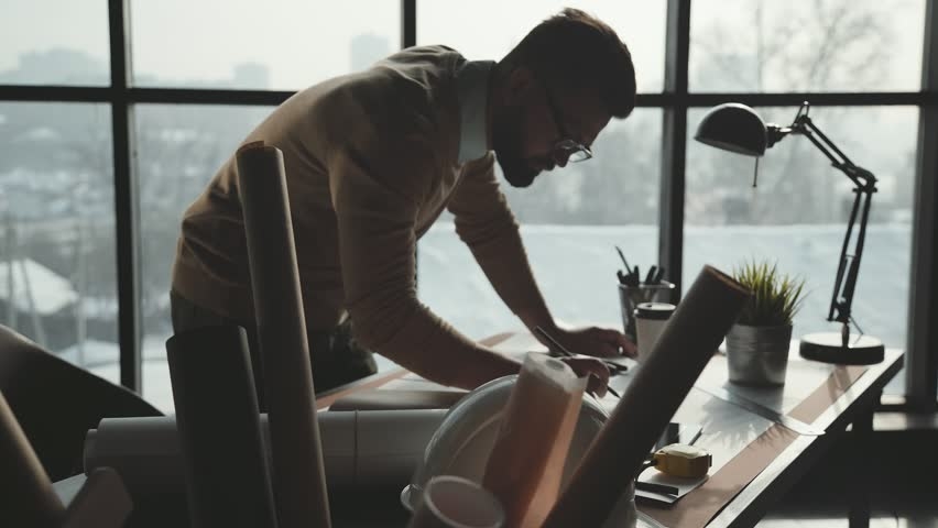 Engineer works in a bright office with a large window, concentrates and draws blueprints. Workplace of an architect or designer: loft style, minimalistic interior, drawings and coffee on the table. | Shutterstock HD Video #1008480181