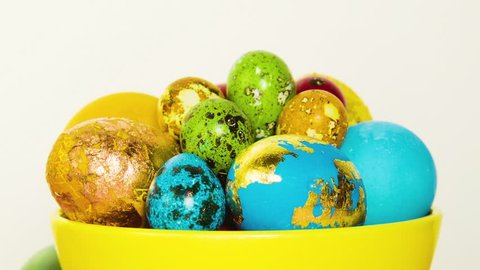 Close-up of Easter beautiful colorful eggs. Eggs lie in a yellow bowl, stand in stands, white background behind. A beautiful Easter composition made of eggs. Move the camera from left to right.