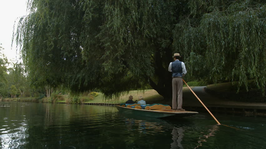 Two woman punting on the river underneath a willow tree.