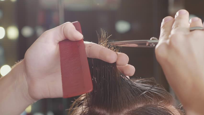 Close-up of barber cuts the hair by scissors at barbershop in slow motion. Hairdresser's hands at working process.