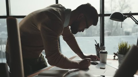 Bearded man in glasses makes sketches in front of large panoramic window. Engineer works in bright office with a large window, concentrates and draws blueprints. Workplace of an architect or designer