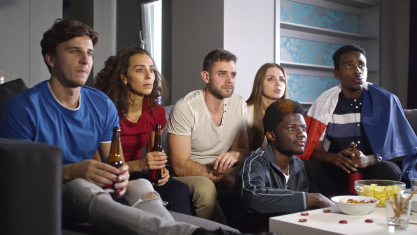Multi-ethnic group of young men and women watching sport match on TV at home, raising arms, yelling, toasting with beer and celebrating goal