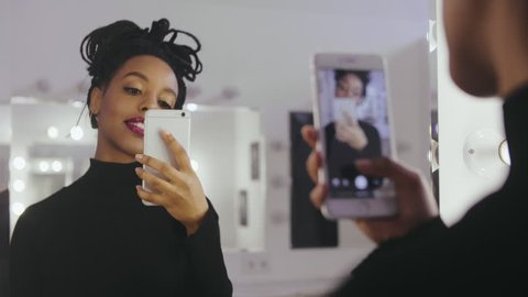 Beauty model photographing its reflection in makeup mirror on mobile phone in dressing room. Young woman using smartphone for selfie photo in makeup room