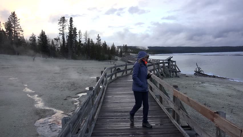 Girl at the boardwalk along the lake Yellowstone in West Thumb Geyser Basin. Wyoming, USA