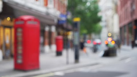 Defocused shot of vintage red telephone booth on London city street. Out of focus shot of people walking through urban streets of London, intended for use as background. 4k