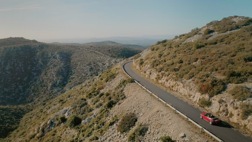 Amazing breathtaking and inspiring to travel and adventure landscape of small mountain road winding in sunset, aerial drone shot of small red cabriolet convertible car explore destination for summer | Shutterstock HD Video #1008626791