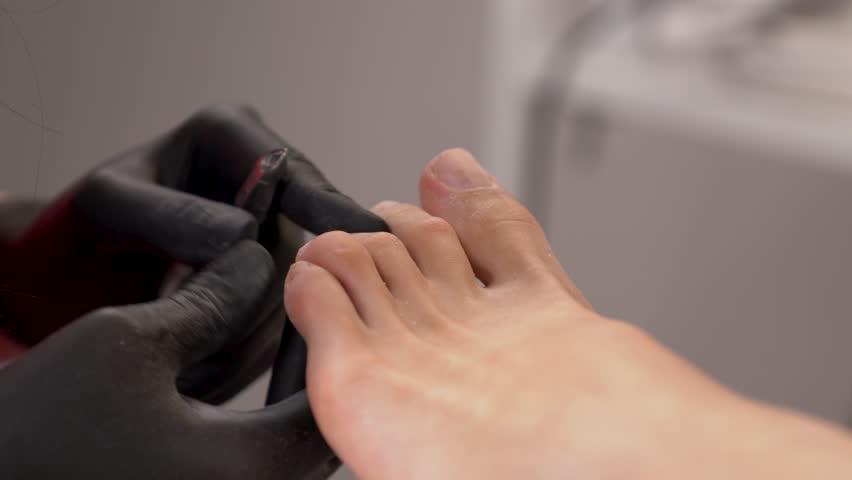 Closeup of manual removing toenail cuticles using nail clippers. Toe nail cuticles cutter.