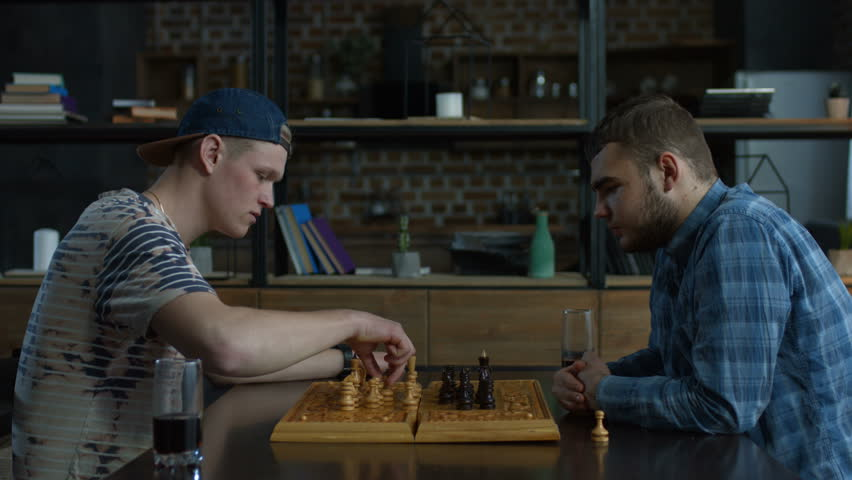 Pensive chess player moving a pawn while playing chess game together with his best friend in domestic interior. Two smart teenagers playing chess game and making moves with chess pieces at home.