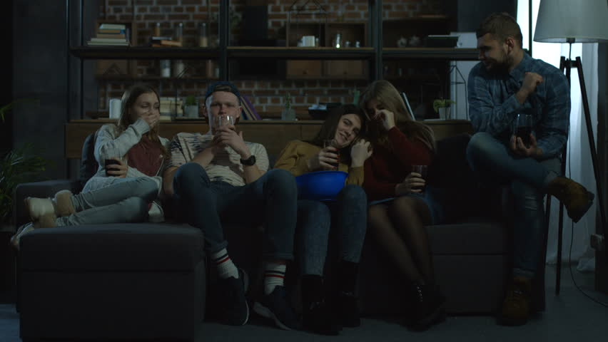 Group of teenage best friends watching horror movie with popcorn at home in the evening while sitting comfortable on sofa. Young hipster teenagers relaxing and watching tv in domestic room.   Shutterstock HD Video #1008668851