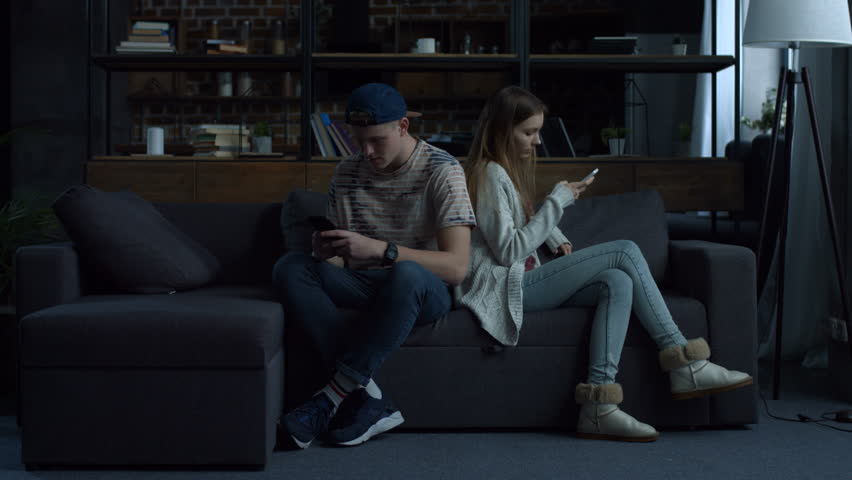 Attractive young couple sitting back to back at home on couch obsessed with smartphones. Couple with mobile phones ignoring each other as strangers, communication problems and social network addiction | Shutterstock HD Video #1008668881