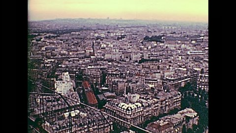 PARIS, FRANCE - CIRCA 1976: Tourists in vintage 70s dress, looking the panorama of Paris from Eiffel Tower. Historic archival footage in Paris city of France in 1970s.