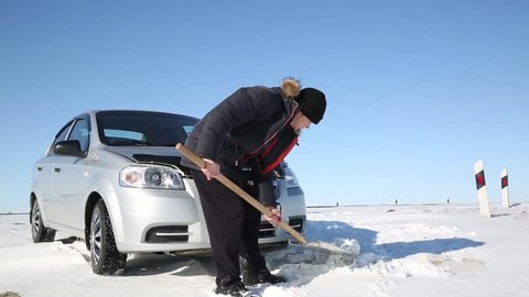 The driver digs out the car with a shovel from the snow. The car is stuck in the snow, the man shovels the snow from under it.