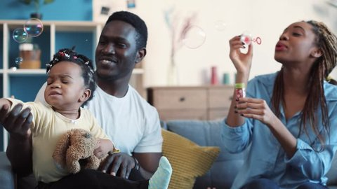 Cheerful African American parents playing with their daughter, father holds the baby, mother blowing soap bubbles, baby-girl tries to catch it. Slow motion, close up view
