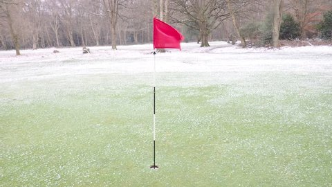 Golf hole flag during snowfall and wind, Hertfordshire, UK