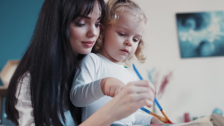 Little child painting on paper book with mum hug sit on sofa together at home