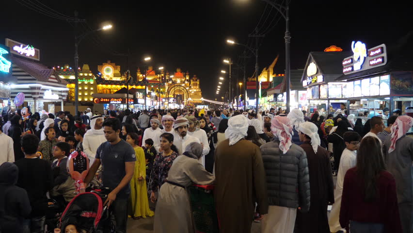 Dubai, UAE - January 12, 2018: People walking past fast food cafe with national cuisine in night amusement park Global Village in Dubai city UAE. Night entertainment park Global Village in Dubai city.