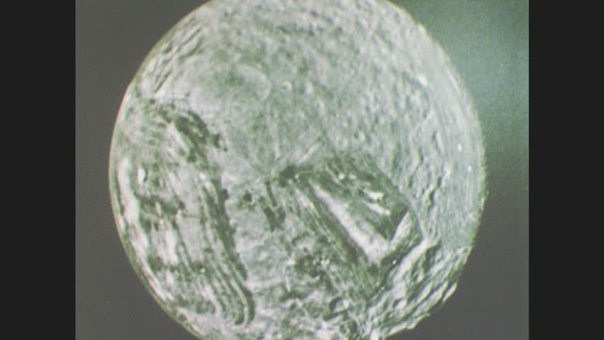 1980s: Image of Uranus' moon Miranda. Man in suit speaks. Man gestures at image of Miranda.