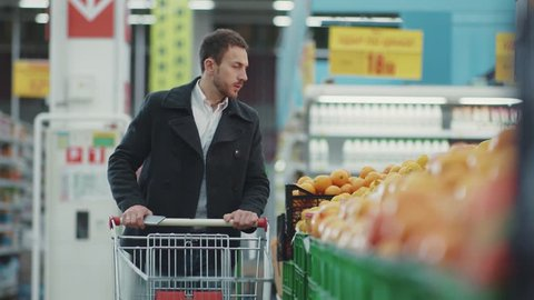Close up young man walking in supermarket with shopping trolley which looking on shopping list in phone choose fruit buyer customer business food face shop store adult market male retail slow motion